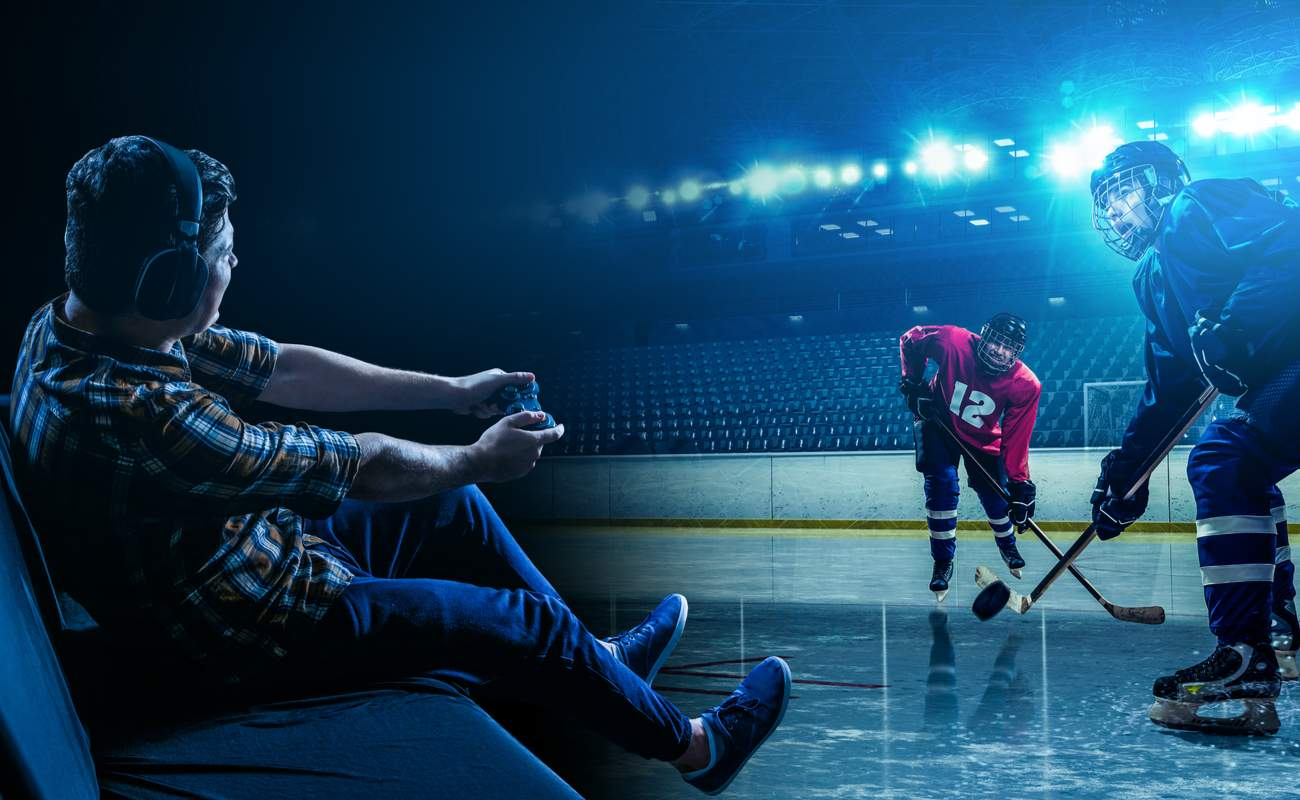 Young man playing a video game ice hockey game with earphones on.