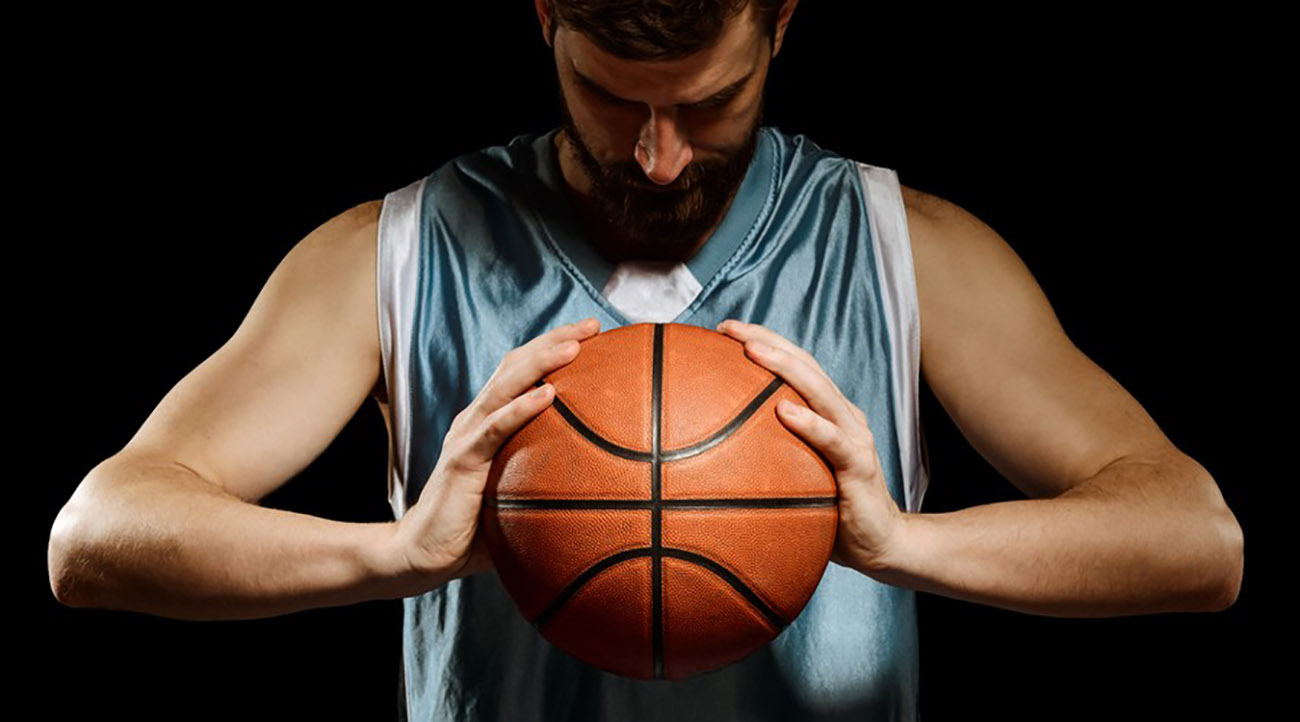 Basketball player looking down and holding a ball
