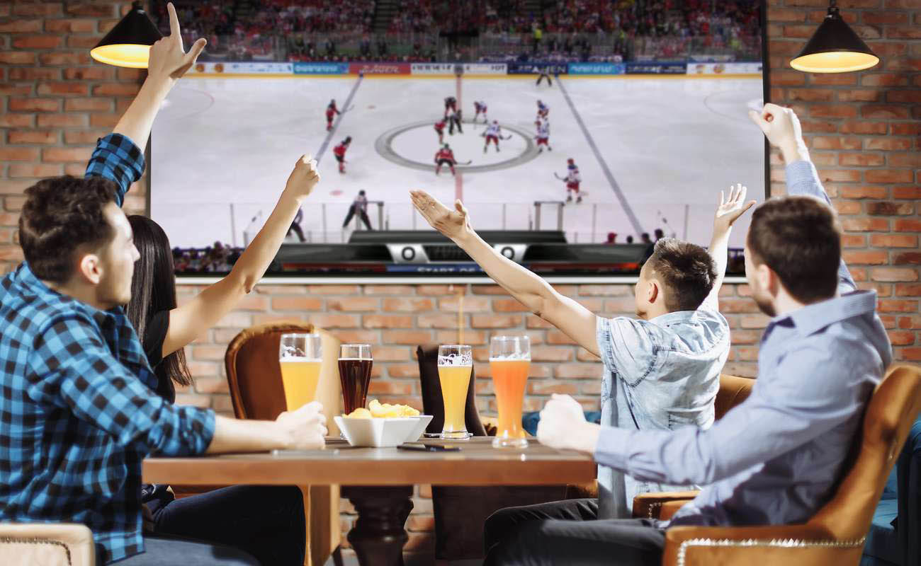 3 men and a woman sitting around the table watching hockey on a big TV