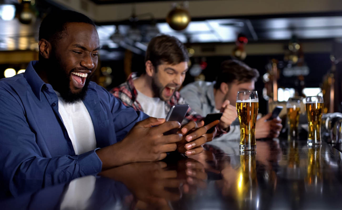 3 men at a bar all on their phones celebrating winning a bet they have placed, each with a pint of beer in front of them
