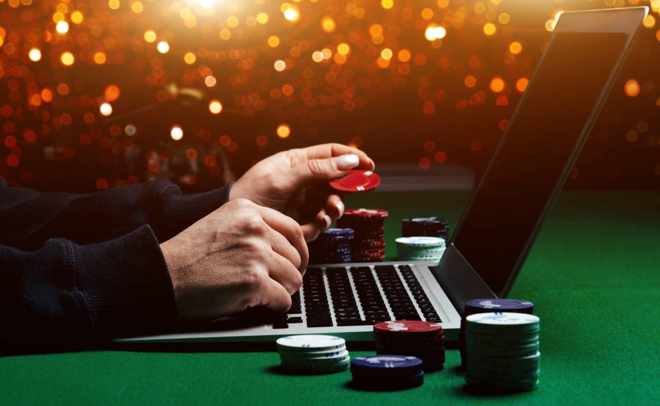 man holding casino chips in front of laptop for online poker