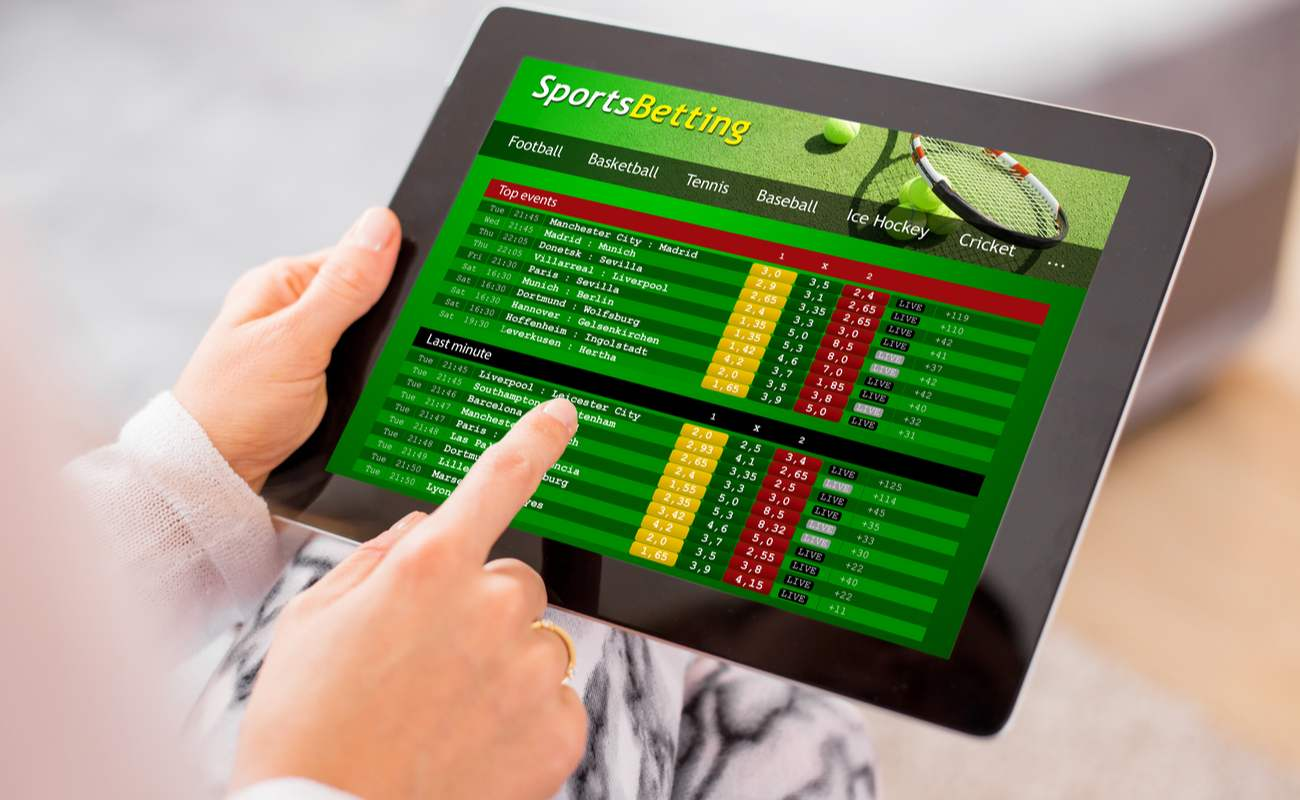 Woman on sports betting app on tablet/iPad with blurred background