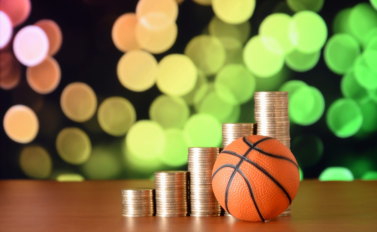 Row of stacked pennies slowly rising up with a basketball in front