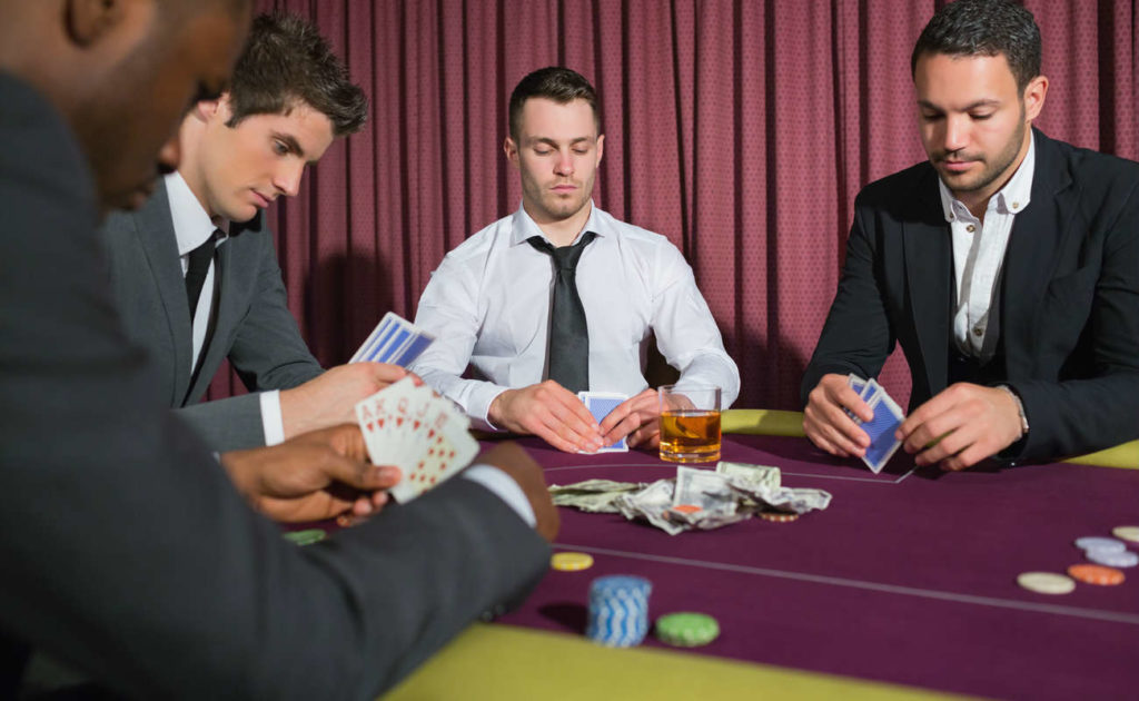 Men playing high stakes poker game in casino