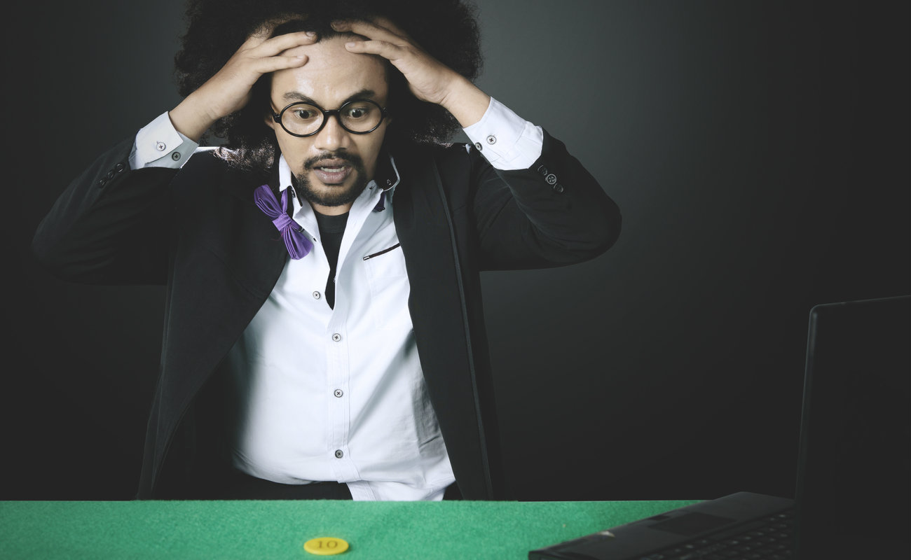 Man loses in online poker gambling with chip and laptop on the table