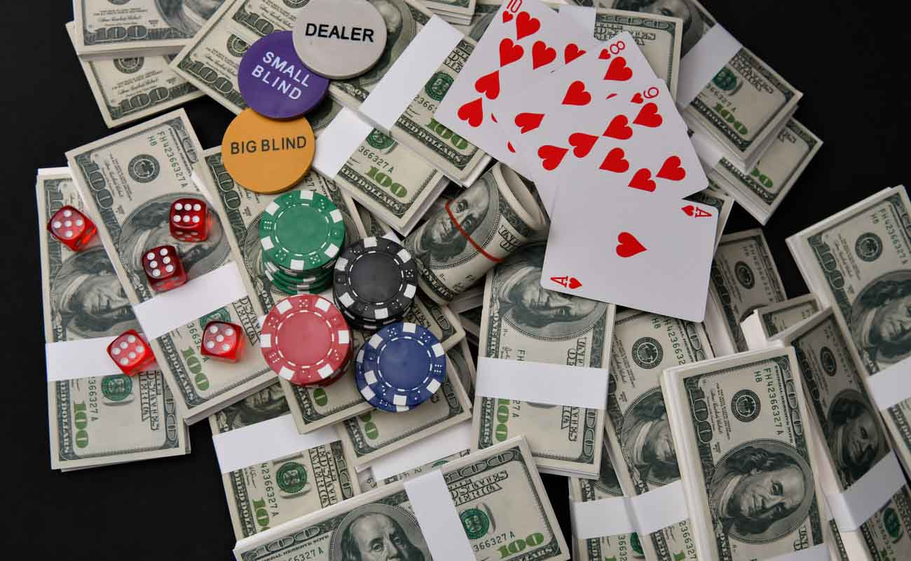 Gaming chips, poker cards, gaming dice and dollars on a dark background.