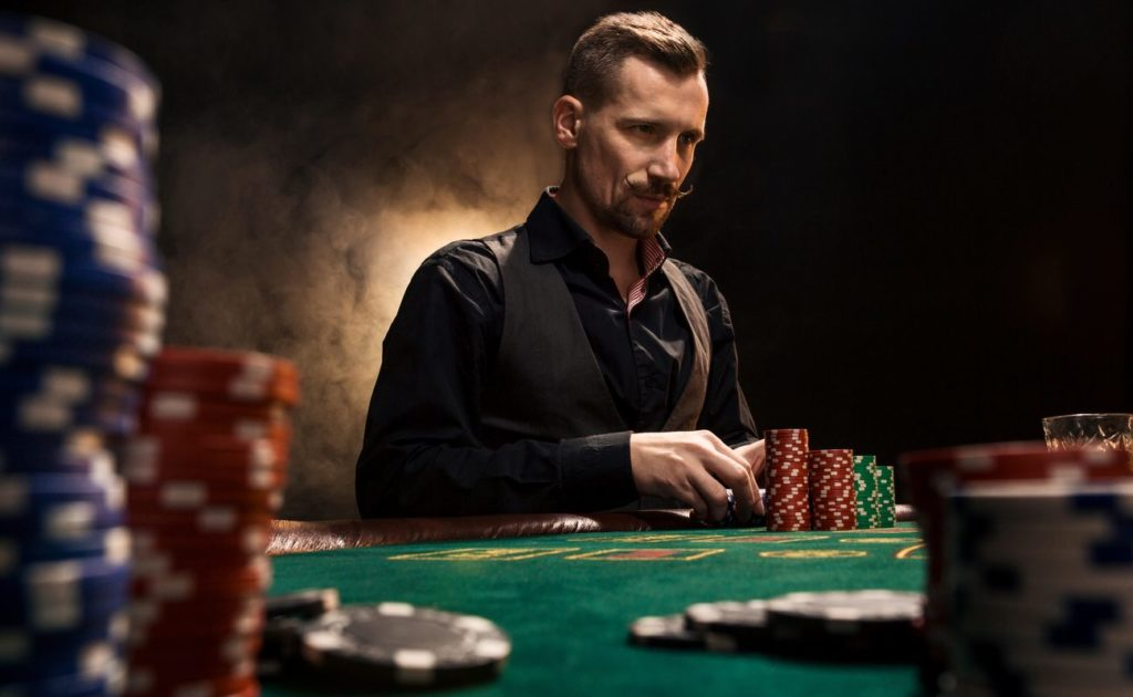 Confident Man Sitting Behind Poker Table With Cards And Chip