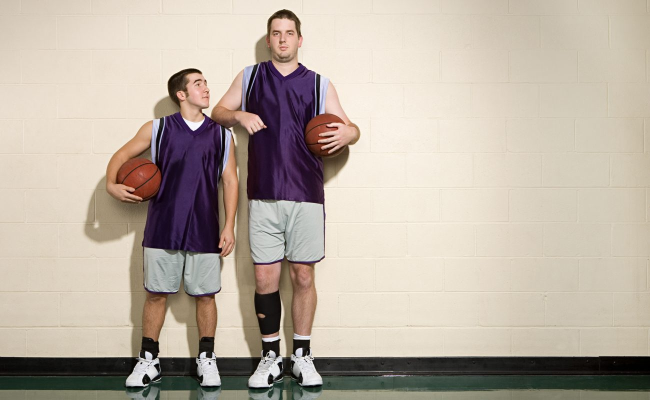 One short and one tall basketball players standing next to each other against a wall, both holding basketballs.