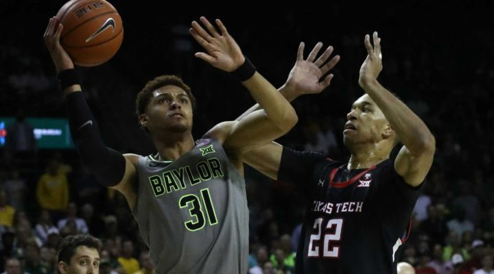 MaCio Teague #31 of the Baylor Bears takes a shot against TJ Holyfield #22 of the Texas Tech Red Raiders in the second half at Ferrell Center