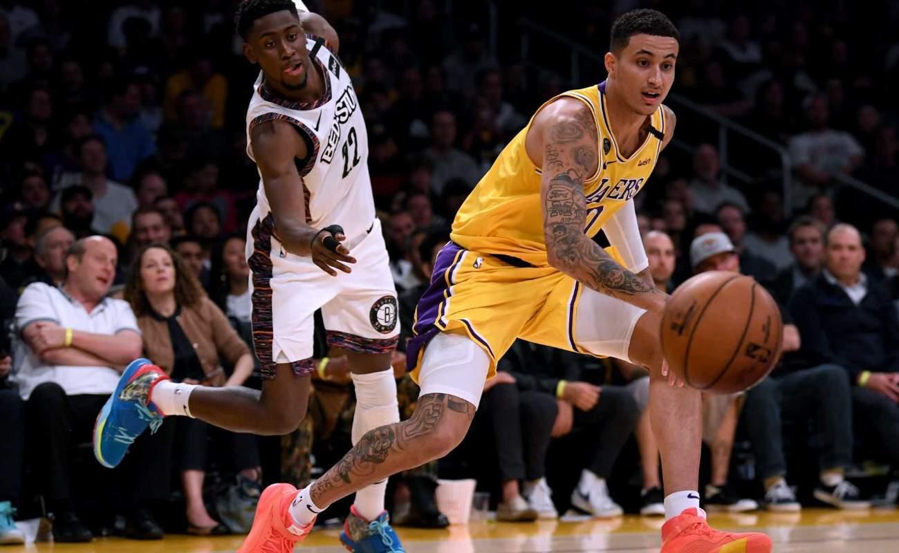 Kyle Kuzma ofLos Angeles Lakers dribbles past Caris LeVert of Brooklyn Nets