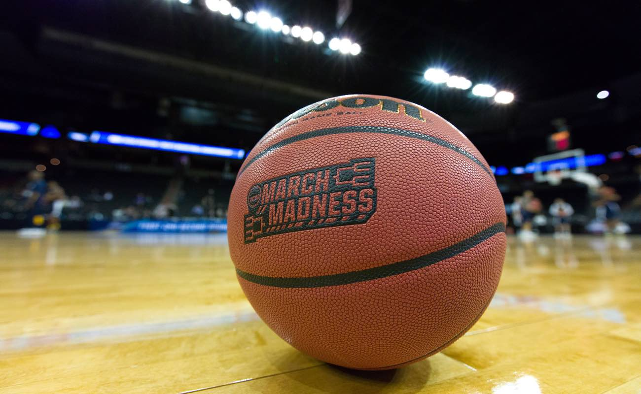 March College Basketball tournament ball sits on court; main focus, stadium background blurred