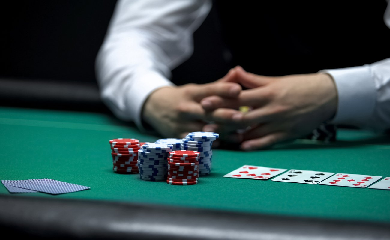 Casino client poker player making bet with all chips