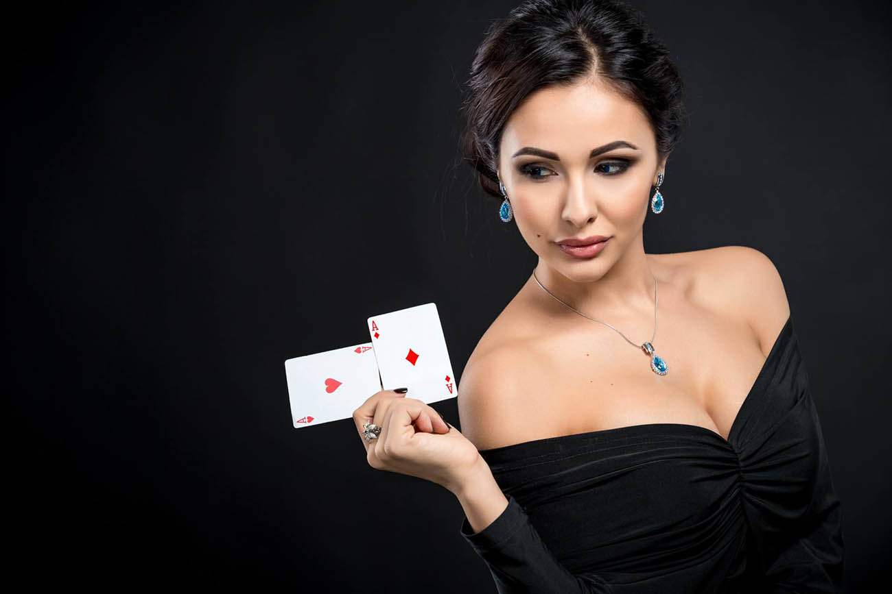 female poker player holding up two aces