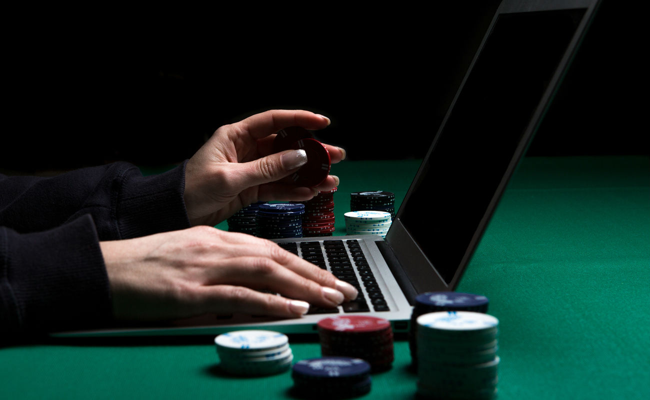Woman playing online poker with laptop on a green table with chips all around