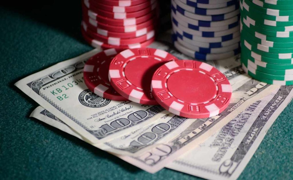 Casino chips and dollar bills on top of table