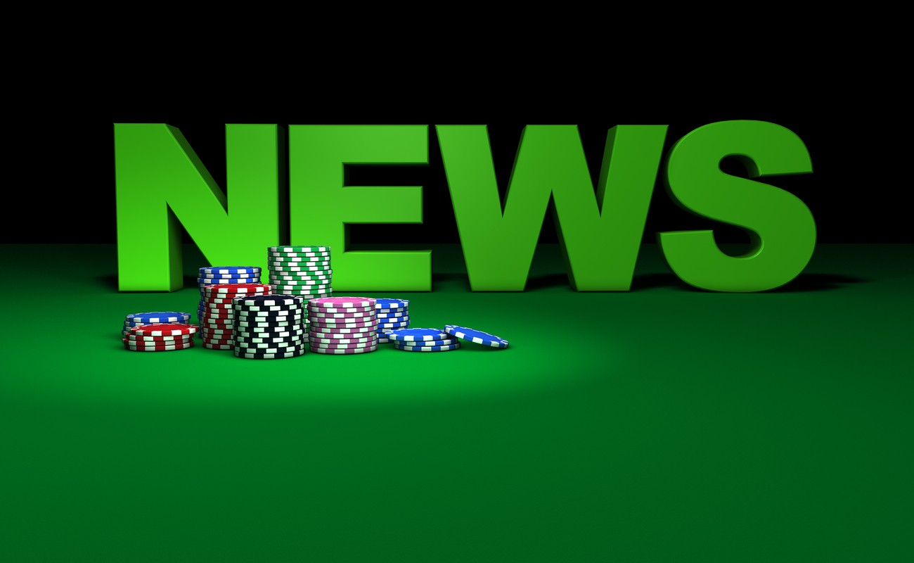colored gambling chips and news sign on green table.