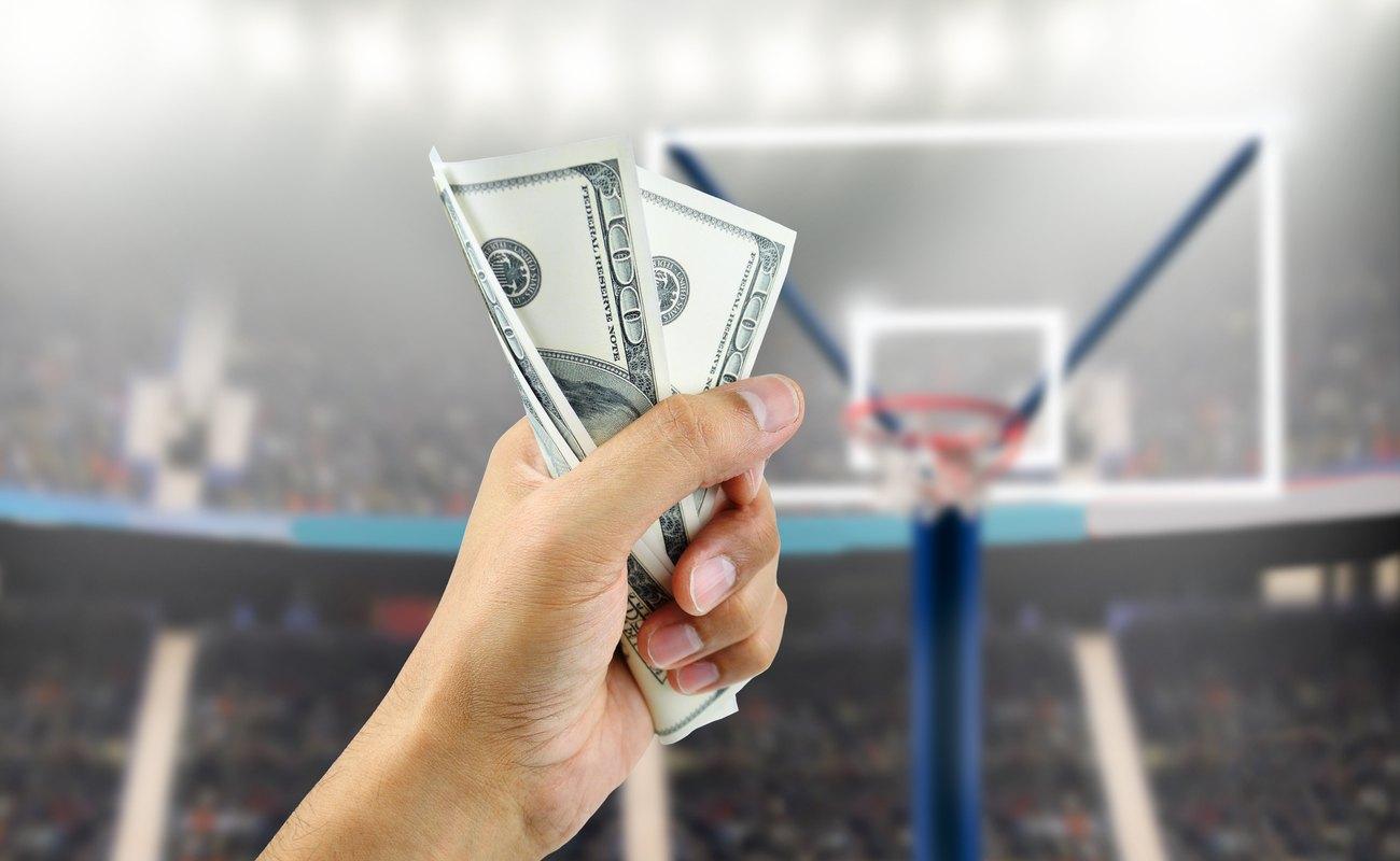 Hand holding money towards a basketball hoop