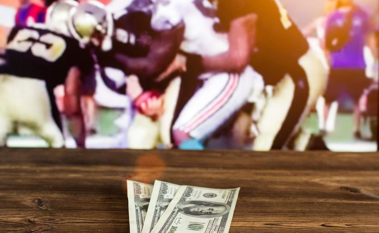 Dollars on a wooden table with a TV in the background showing American football