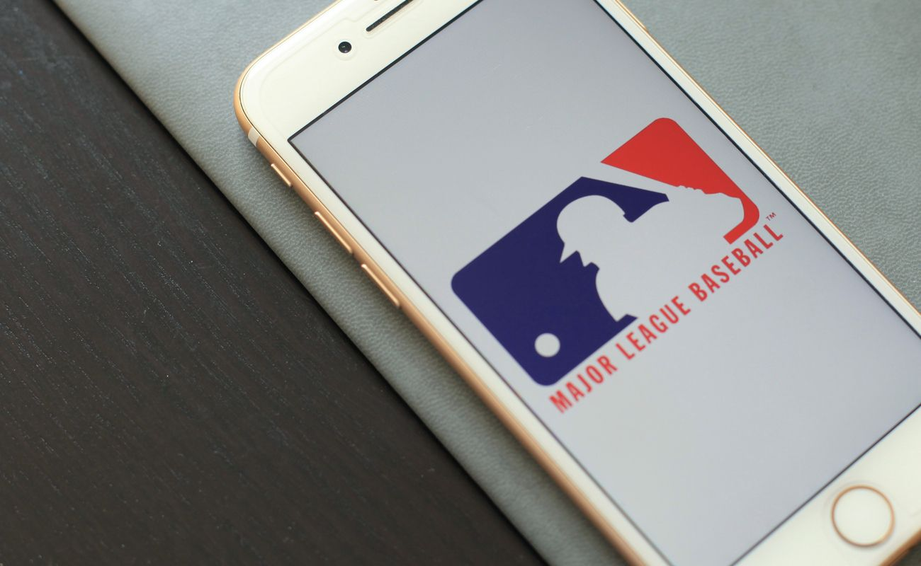 The official logo of the Major League Baseball in an iPhone screen