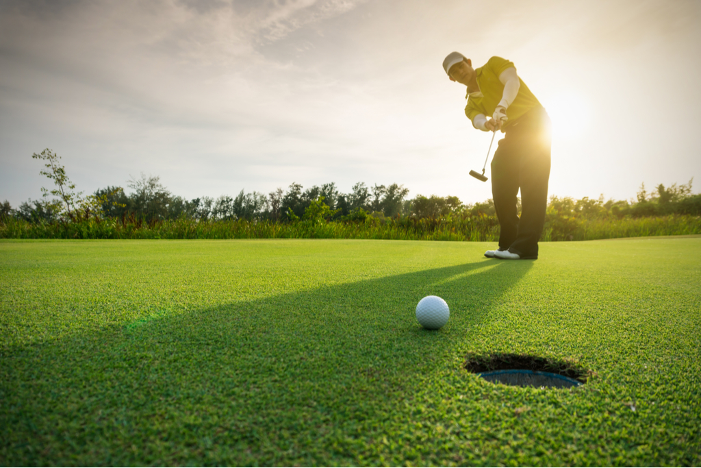 Golf player shooting the ball towards the hole with the sun in the background