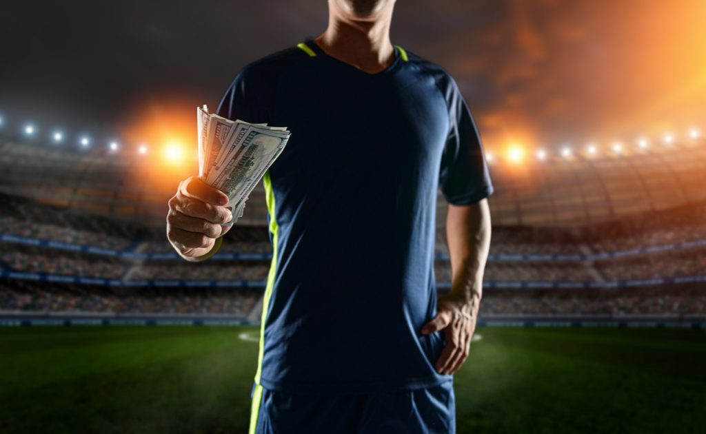 Soccer player holding money notes at soccer stadium