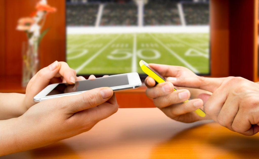 Friends using mobile phone and betting during an American football match