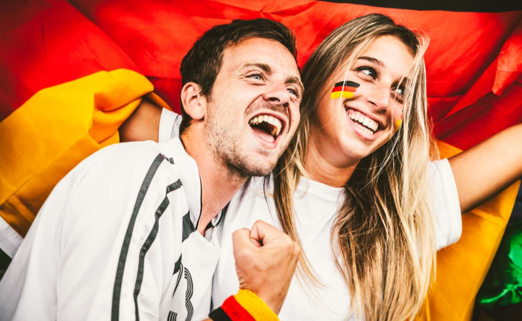 Soccer fans at a stadium with flags painted on their cheeks, cheering their teams
