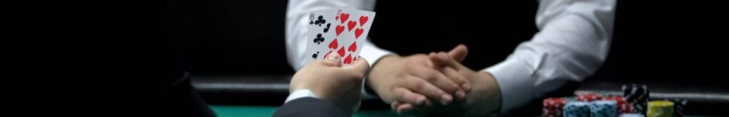 Poker player looks at his hole cards dealt by the croupier at the poker table