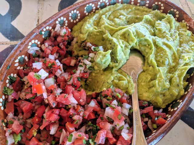 Massive amount of guacamole and pico de gallo.
