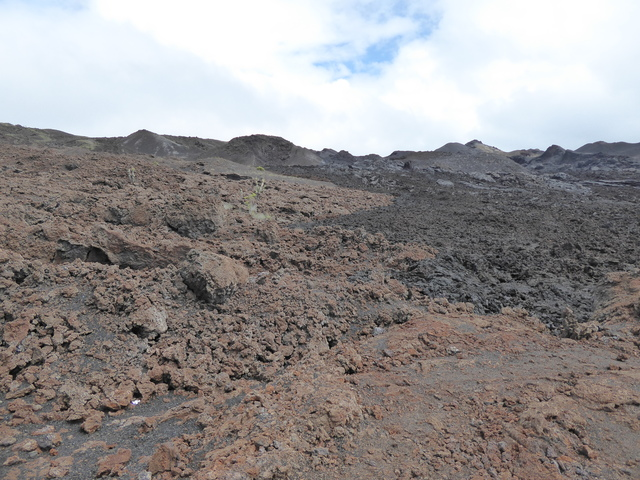 On the left the lava is older, oxidation has caused it to turn reddish-brown. On the right, you can see newer lava, which is closer to black.