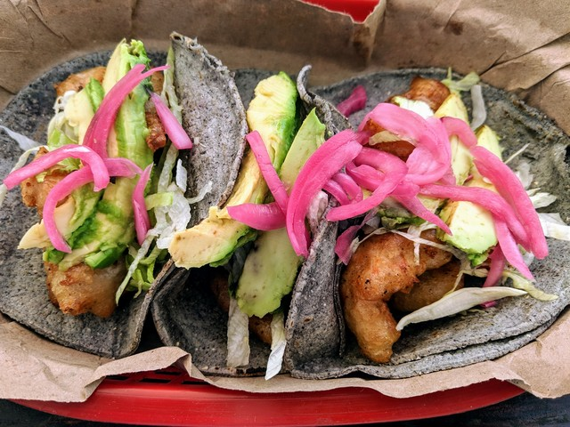 Fried shrimp tacos with pickled red onion and avocado on blue corn tortillas