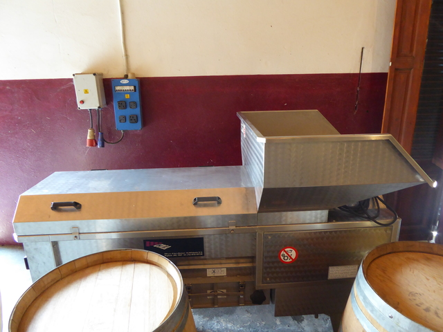 The first step of wine making is putting the grapes through this press.