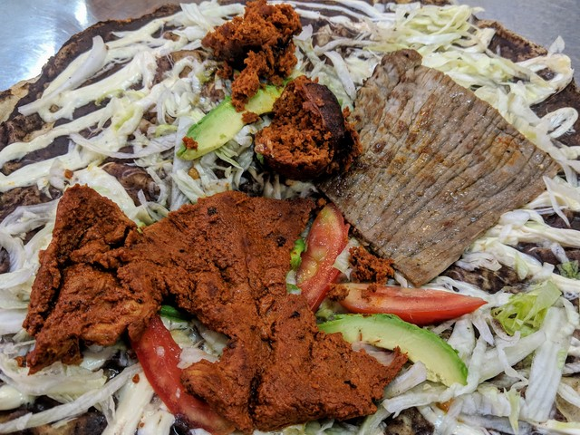 Tlayuda with chorize, marinated pork and carne asada.