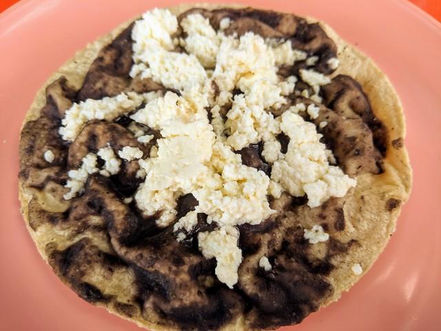 A memela, fresh masa corn tortilla, black beans and queso fresco.