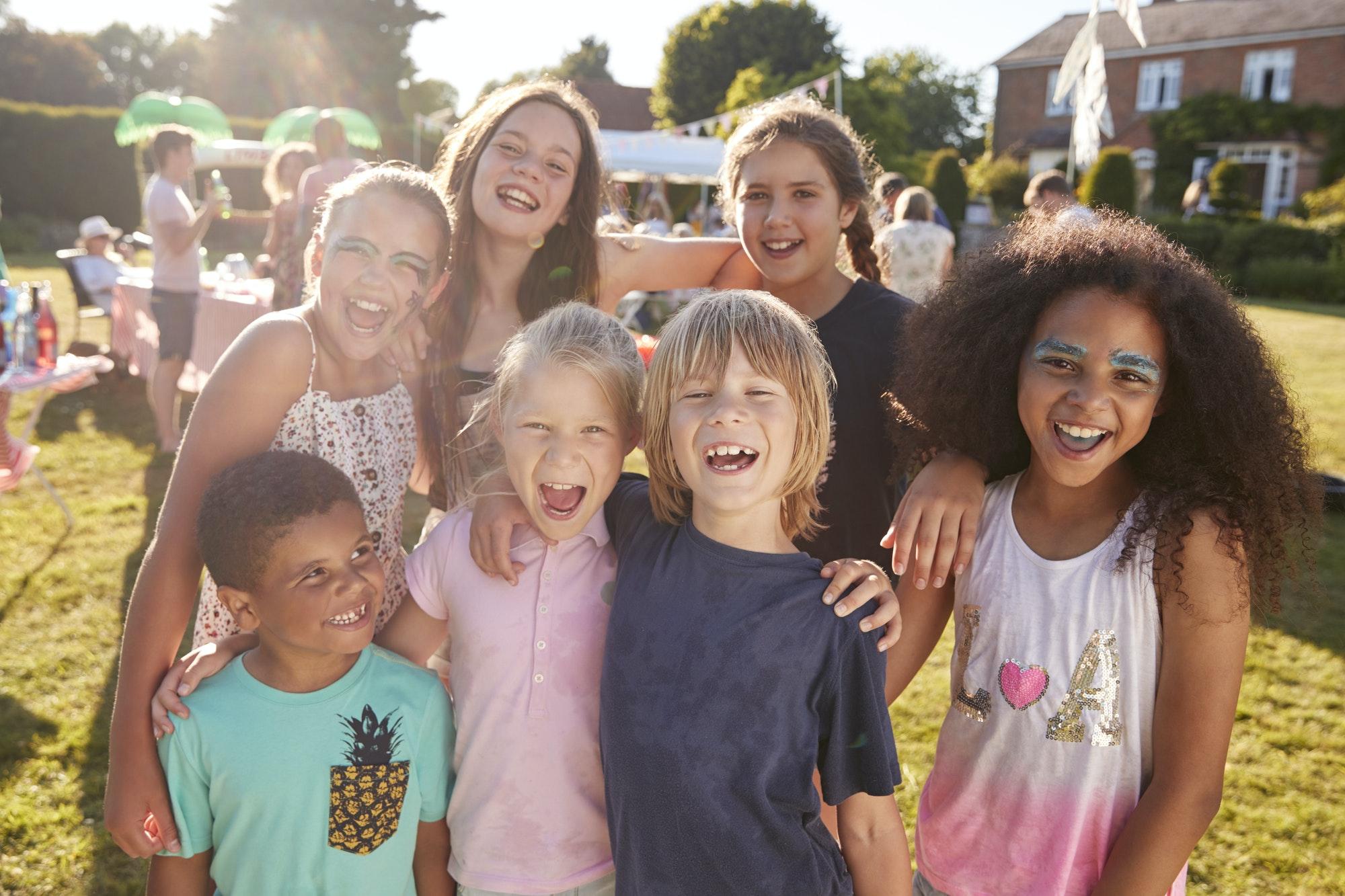 Portrait Of Excited Children At Summer Garden Fete