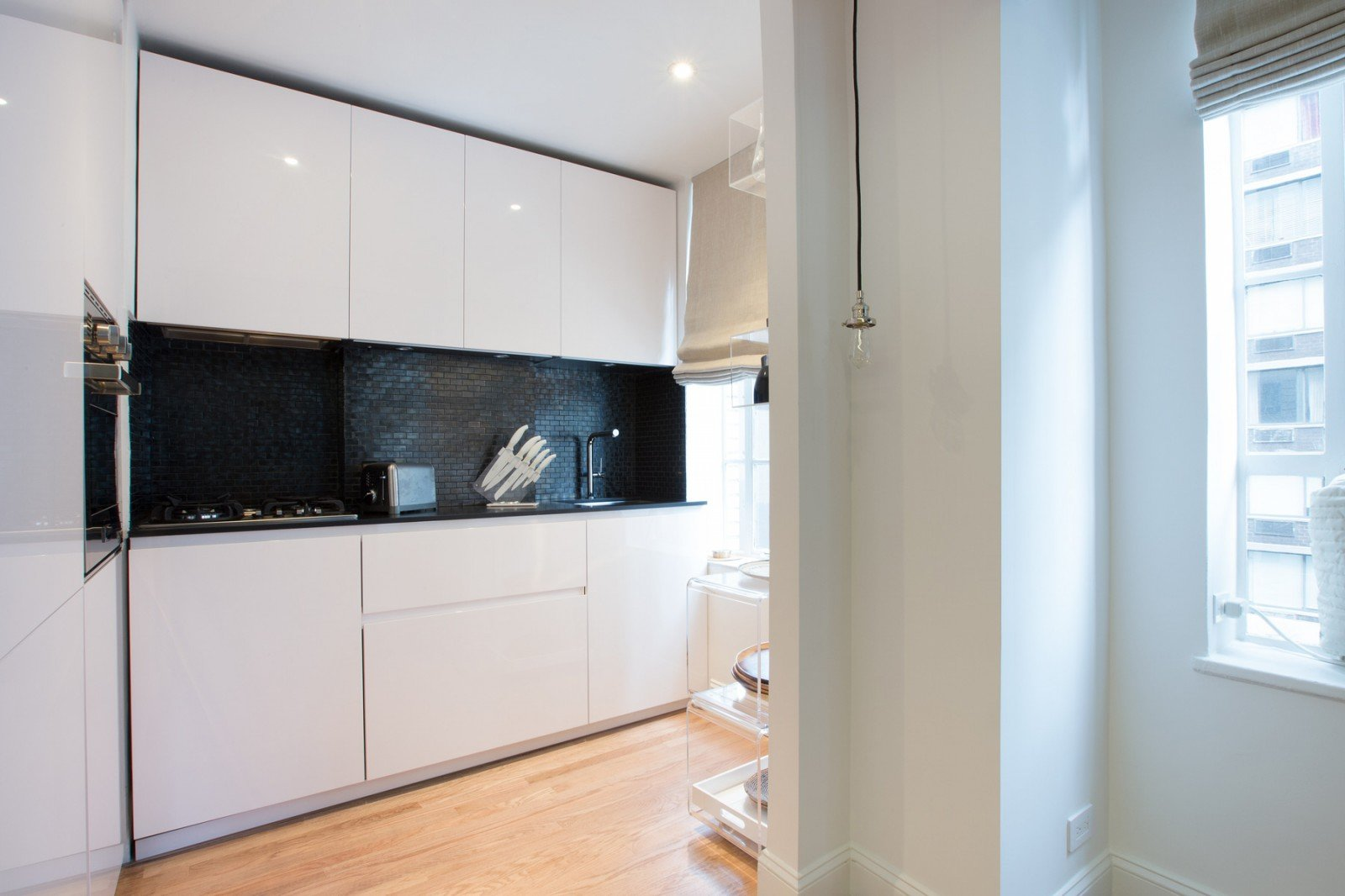 The kitchen features glossy white lacquer cabinets