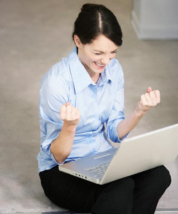 Femme contente devant son ordinateur