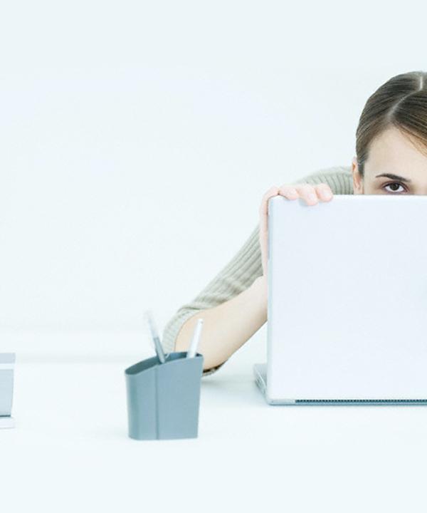 Femme cachée derrière son ordinateur