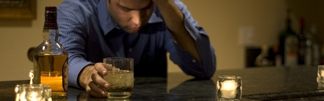 A man wearing a blue shirt drinking an ice cold glass of whiskey.