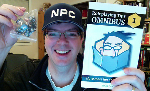 Johnn holding the Omnibus book and dice prizes