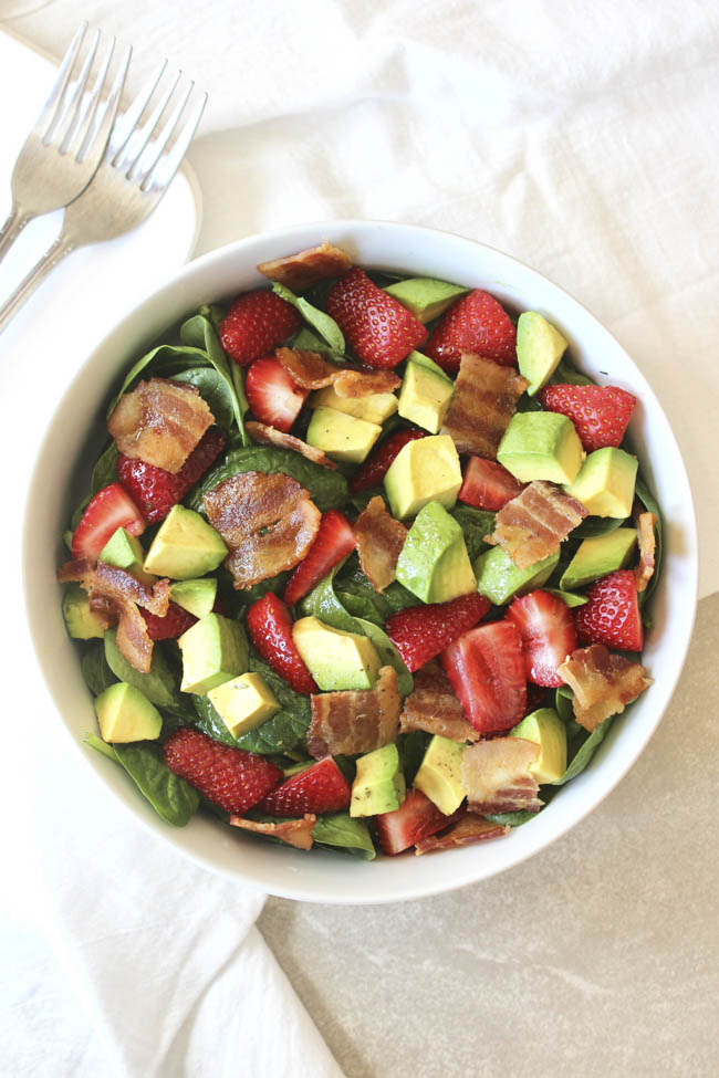Juicy strawberries add a welcomed burst of freshness and sweetness in any meal. Enjoy them studded in this salad, with crisp spinach, creamy avocado, and salty bacon. We love them coated in the vinaigrette!
