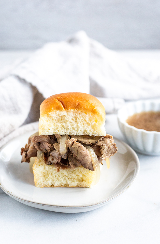 roast beef in a bun with onions on a small plate with dipping broth - french dip sandwich