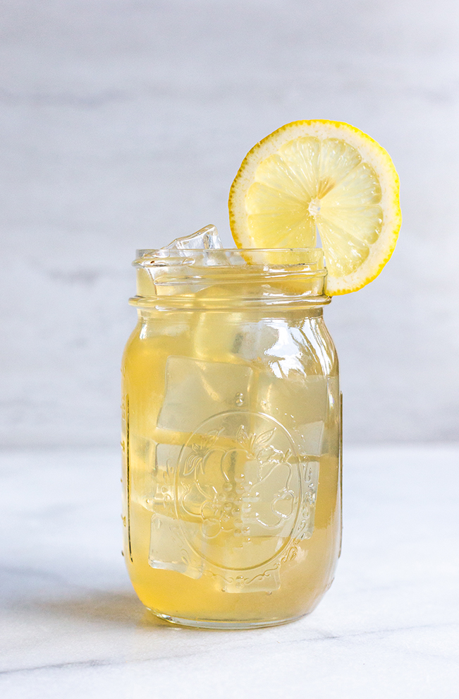 whiskey lemonade with a grey background and a lemon slice