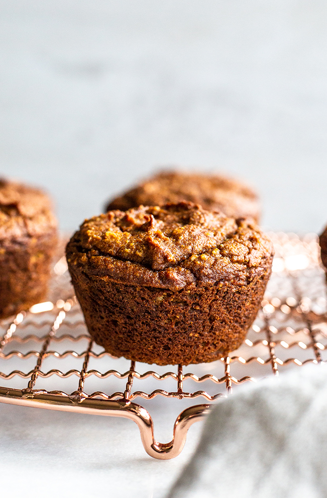 pumpkin muffins on a copper cooling rack with a linen towel on a white background