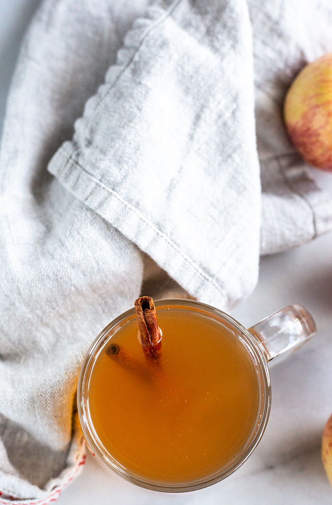 apple tea with a cinnamon stick with a linen napkin