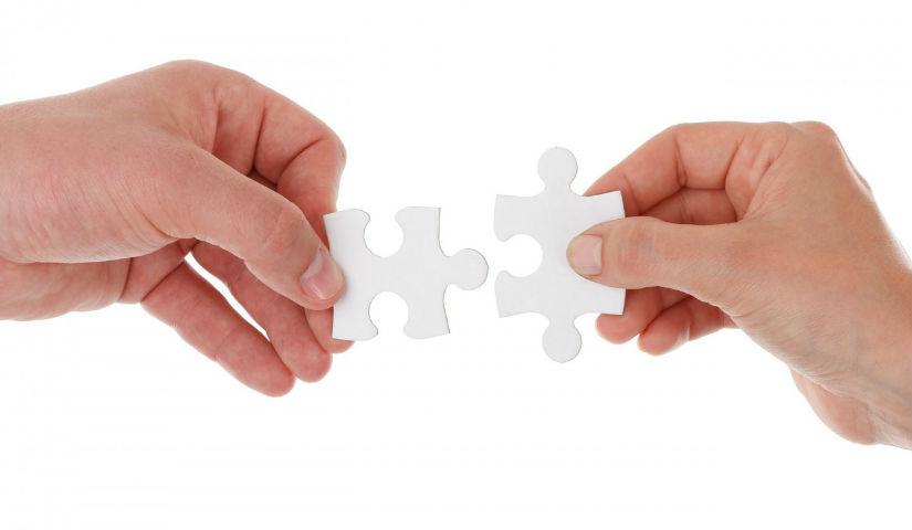 Imagen de dos manos uniendo piezas de rompecabezas