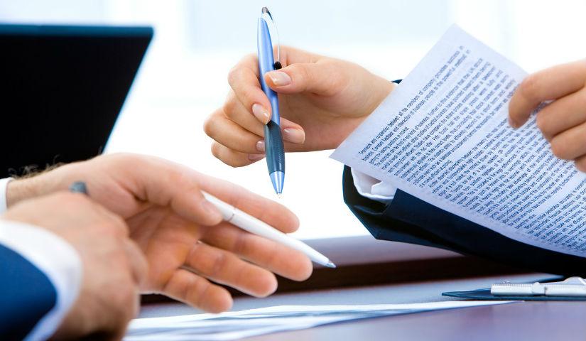 Imagen de las manos de dos personas firmando documentos