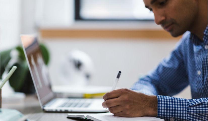 Imagen de un hombre escribiendo en una libreta