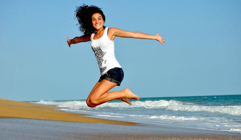 Imagen de una mujer saltando en la playa