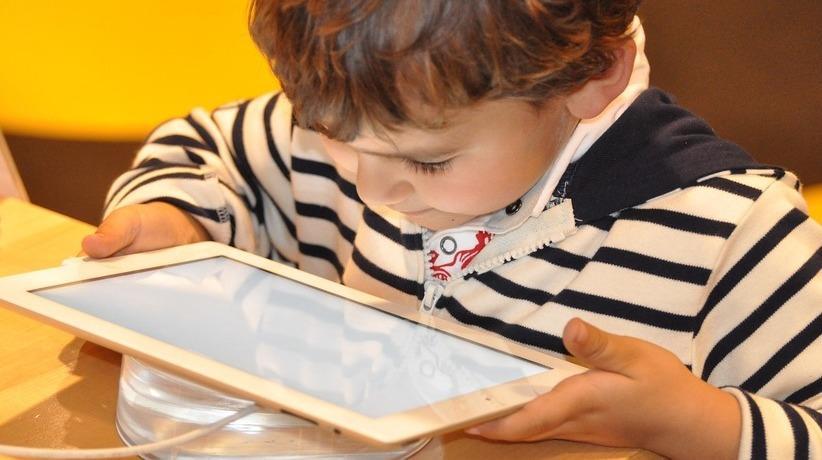 Imagen de un niño mirando fijamente una tablet